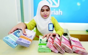 File photo shows an employee of BRI Syariah bank managing bundle of Indonesian Rupiah bank notes in Jakarta. Indonesian regulators have launched a plan aimed at growing the Islamic finance sector, which currently accounts for less than five percent of banking assets, compared to a quarter in neighbouring, more developed Muslim-majority Malaysia and around half in Saudi Arabia. (AFP)