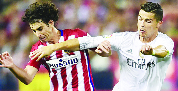 Atletico Madrid's Portuguese midfielder Tiago (left), vies with Real Madrid's Portuguese forward Cristiano Ronaldo during the Spanish League football match Club Atletico de Madrid vs Real Madrid CF at the Vicente Calderon Stadium in Madrid on Oct 4. (AFP)
