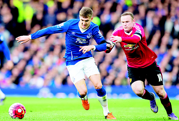 Manchester United's Wayne Rooney (right), grabs a hold of Everton's John Stones during the English Premier League soccer match between Everton and Manchester United at Goodison Park Stadium, Liverpool, England on Oct 17. (AP)