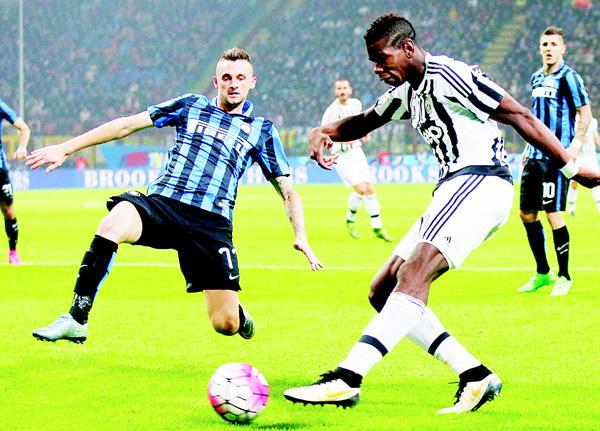 Juventus' Paul Pogba (right), kicks the ball past Inter Milan's Marcelo Brozovic during a Serie A soccer match between Inter Milan and Juventus at the San Siro Stadium in Milan, Italy on Oct 18. (AP)