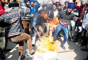 Kashmiri Sikhs kick a burning effigy of Gurmeet Ram Rahim Singh, chief of the religious sect Dera Sacha Sauda, during a protest against the killing of two Sikh boys,