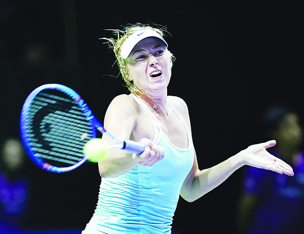 Maria Sharapova of Russia makes a forehand return against Simona Halep of Romania during their singles match at the WTA tennis finals in Singapore on Oct 27. (AP)