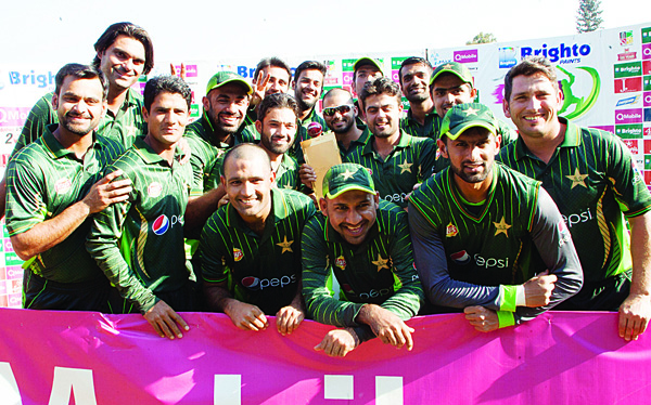 Pakistan's players celebrate with the series trophy after their victory in the final game in a series of three ODI cricket matches between Pakistan and hosts Zimbabwe at the Harare Sports Club on Oct 5. (AFP)