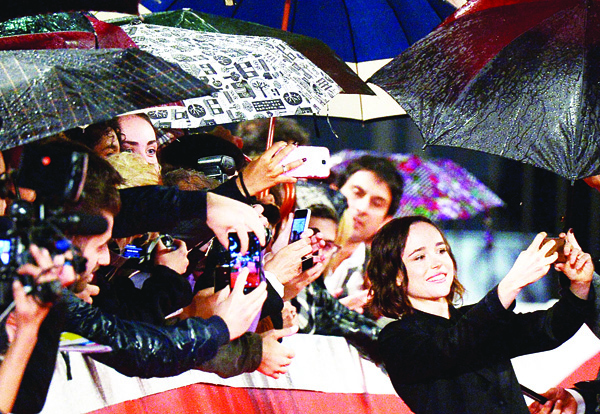 Canadian actress Ellen Page (right), snaps a selfie with fans on the red carpet before the screening of the movie 'Freeheld' at the 10th Rome Film Festival on Oct 18, in Rome. (AFP)