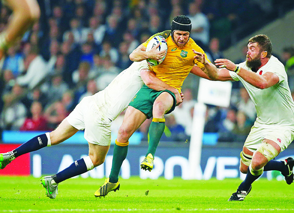 Australia's Matt Giteau (center), is tackled during the Rugby World Cup Pool A match between England and Australia at Twickenham stadium in London, Oct 3. (AP)