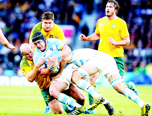 Argentina's Marcos Ayerza is tackled by Australia's Stephen Moore during their Rugby World Cup semifinal match at Twickenham Stadium London, on Oct 25. (AP)