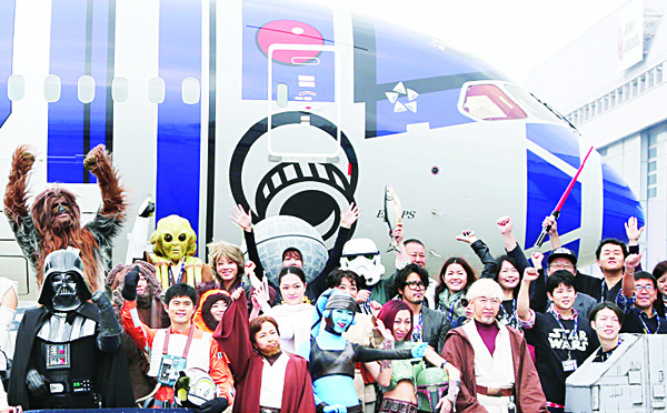 Fans dressed in costumes of Star Wars characters pose for a photo in front of the All Nippon Airways (ANA) special plane painted like R2-D2 before boarding it at Haneda international airport in Tokyo. The Boeing 787 decorated with blue and silver pattern of R2-D2 will be put on ANA's normal operation bound for Vancouver starting from Sunday. This is a part of ANA Star Wars project. The Japanese airline company announced earlier this year that it closed contract with Walt Disney Japan to use Star Wars characters until 2020. (AP)