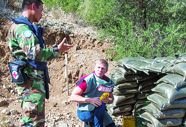 In this photo released by the United Nations in Cyprus (UNFICYP) on Oct 13, the British actor Daniel Craig speaks with a UN specialist mine detecting team member at the minefields in the UN controlled buffer zone on the divided island of Cyprus. (AP)