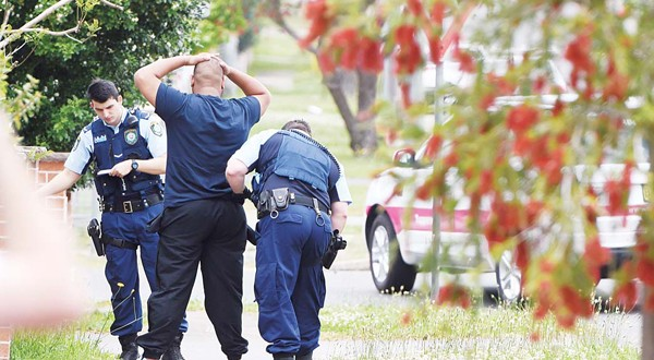 Police pull over and search a man and his vehicle near a house which was raided earlier Wednesday morning on Bursill Street at Guildford in Sydney's west, on Oct 7. (Inset): Women walk past a home where police are conducting a search in the suburb of Guildford in Sydney on Wednesday. (AP)