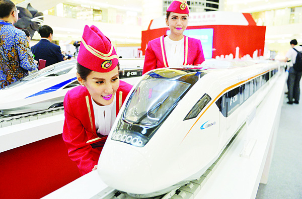 In this photo taken on Aug 13, 2015, Indonesian models look at scale models of Chinese-made bullet trains on exhibition at a shopping mall in Jakarta. Chinese and Indonesian state-owned companies on Oct 16 signed a $5.5 billion deal to build the first high-speed railway in Southeast Asia's top economy, after Beijing beat Tokyo to win the construction project. (AFP)