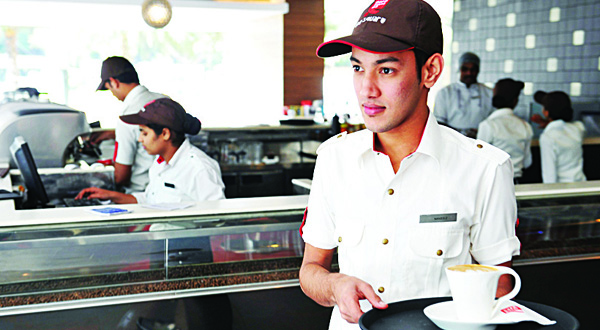 A member of staff at the Indian coffee retail chain CafÈ Coffee Day serves coffee at an outlet in Bangalore on Oct 14, 2015. India's CafÈ Coffee Day chain launched the country's largest stock market flotation in nearly three years on Oct 14, seeking to fend off Starbucks as it taps the tea-loving nation's growing taste for coffee. (AFP)