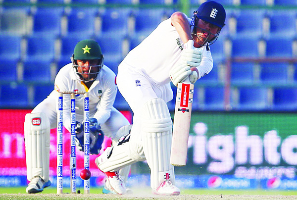 England's Alastair Cook (right), is watched by Pakistan's wicketkeeper Sarfraz Ahmed as he plays a shot during the fourth day's play of the first cricket Test match between Pakistan and England at The Sheikh Zayed International Cricket Stadium in Abu Dhabi on Oct 16. (AFP)