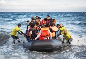 Four lifeguards from Barcelona, Spain, working as volunteers, help disembarking a dinghy as migrants and refugees arrive from the Turkish coasts to the northeastern Greek island of Lesbos
