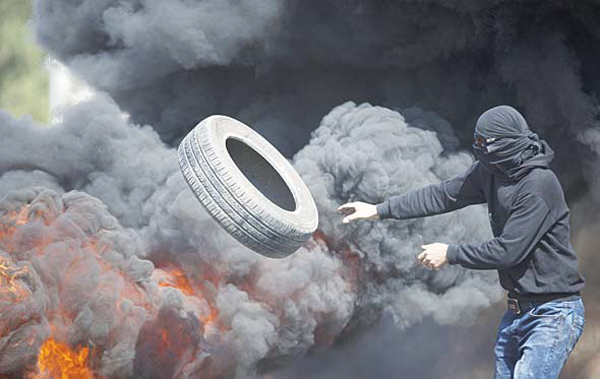 Palestinians burn tires during clashes with Israeli troops near Ramallah, West Bank on Oct 16. Tensions and violence have been mounting in recent weeks, in part fueled by Palestinian fears that Israel is trying to expand its presence at a major Muslim-run shrine in Jerusalem, a claim Israel has denied. (AP)
