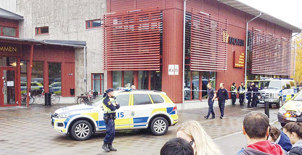 Swedish police officers secure the area outside a primary and middle school in Trollhattan, southwestern Sweden, on Oct 22, where a masked man armed with a sword injured an adult and four students before being arrested by police. (AFP)