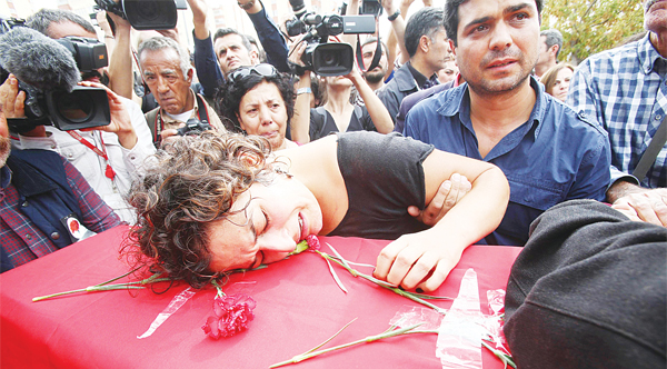 A relative mourns over the coffin of Korkmaz Tedik, a board member of the Turkish Labour Party (EMEP), who was killed in twin bombings in Ankara the day before, during his funeral in the capital on Oct 11. Turkey woke in mourning on Oct 11 after at least 128 people were killed by suspected suicide bombers at a peace rally of leftist and pro-Kurdish activists in Ankara, the deadliest such attack in the country's recent history. (AFP)