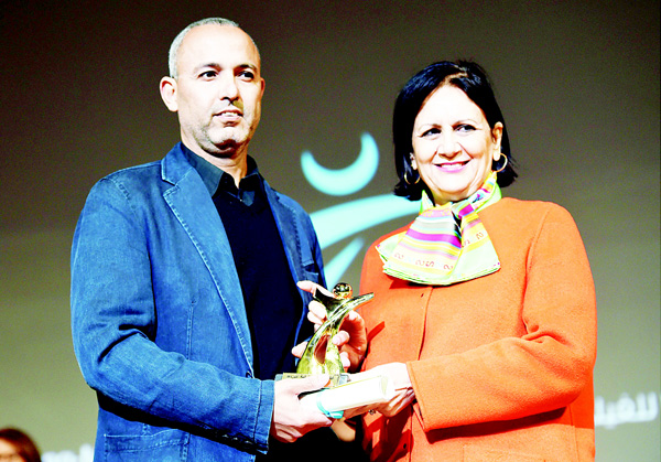 Moroccan director Mohamed Mouftakir (left), receives from Tunisian Culture Minister Latifa Lakhdar the Golden Tanit award for his film 'L'orchestre des Aveugles' during the closing ceremony of the 26th Carthage Film Festival on Nov 28, in the Tunisian capital Tunis. (AFP)