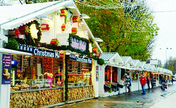 People walk past a food stand on the reopening day of the Paris Christmas market on the Champs-Elysees avenue on  Nov 19. (AFP)