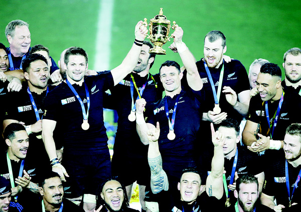 New Zealand All Blacks captain Richie McCaw (left), and Dan Carter hold the Webb Ellis trophy aloft as their teammates celebrate after their Rugby World Cup final win over Australia at Twickenham Stadium, London, on Oct 31. (AP)