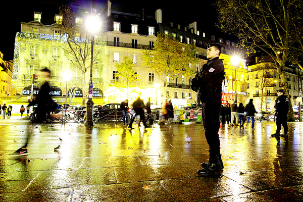 French gendarms (right), enforcing the Vigipirate plan, France's national security alert system, are pictured on Nov 19, on Place Saint-Michel in Paris. France revealed on Nov 19 it will spend an extra 600 million euros ($641 million) next year to ramp up security after the Paris attacks. President Francois Hollande announced this week that France is freezing plans to cut troop numbers through 2019. At the same time, the country will add 8,500 law enforcement jobs including 5,000 new police. (AFP)