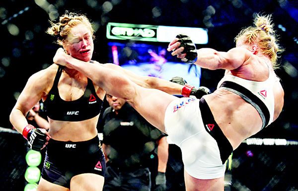 Holly Holm of the US (right), lands a kick to the neck to knock out compatriot Rousey and win the UFC title fight in Melbourne on Nov 15. (AFP)