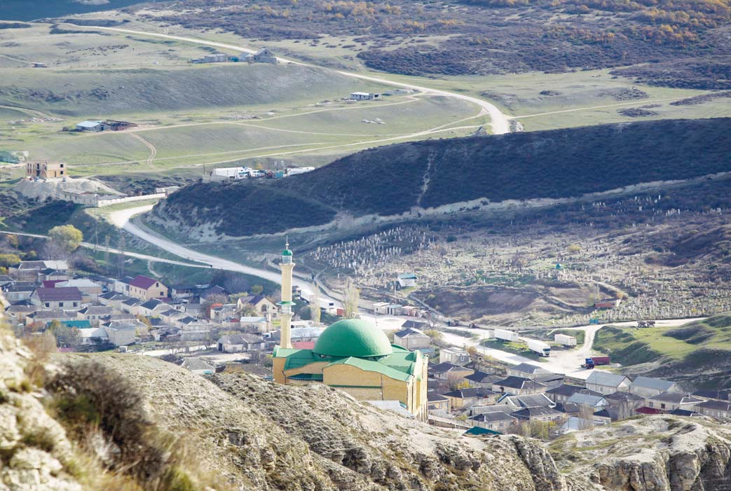 In this photo taken on `Nov 12, a mosque is seen from the mountains in the village of Gubden, Dagestan, Russia. An epidemic of recruitment for the Islamic State group has swept through the predominantly Muslim Dagestan where  young men and women are leaving for Syria, pursuing a religious ideal or trying to escape police profiling. (Inset): In this photo taken on Nov 12, Abdulla  Magomedov, brother of Rashid Magomedov who left to become an Islamic State fighter and was killed in Syria, sits at home in the village of Komsomolskoye, Dagestan, Russia. (AP)