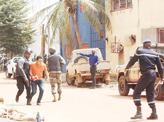 A Mali trooper (left), assists a hostage (second left), to leave the scene, from the Radisson Blu Hotel to safety after gunmen attacked the hotel in Bamako, Mali on Nov 20. (AP)