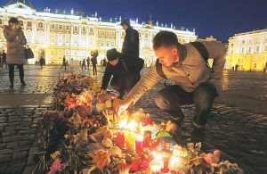 A man lights a candle in memory of the plane crash victims at Dvortsovaya (Palace) Square in St Petersburg, Russia on Nov 3. Mourners continue to come to St Petersburg's Pulkovo Airport and Dvortsovaya Square on Tuesday to lay flowers and leave paper planes and soft toys at the arrivals hall. (AP)