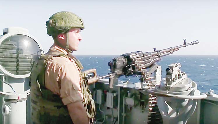 A Russian seaman stands next to a machine gun on the Russian missile cruiser Moskva, near the shores of Syria's province of Latakia