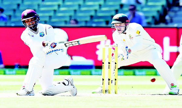 West Indies' Denesh Ramdin (left), hits a shot as Australia's Peter Nevill looks on during their cricket Test match in Melbourne, Australia on Dec 29. (AP)