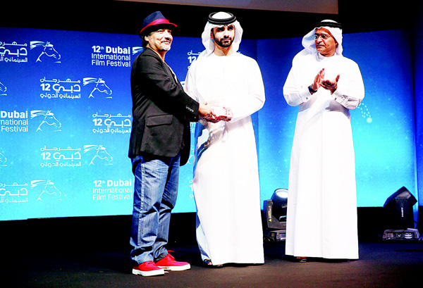 Egyptian director Mahmood Soliman receives the best director Muhr award from Sheikh Mansoor bin Mohammed bin Rashid al-Maktoum (center), during the closing ceremony of the annual Dubai International Film Festival on Dec 16, in the Gulf emirate.