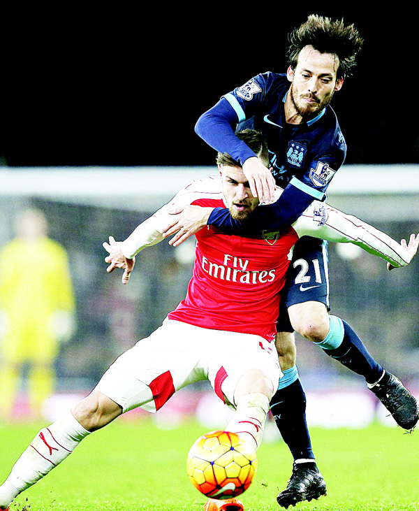 Arsenal's Welsh midfielder Aaron Ramsey (left), vies with Manchester City's Spanish midfielder David Silva, leading to a foul awarded against Ramsey, during the English Premier League football match between Arsenal and Manchester City at the Emirates Stadium in London on Dec 21. (AFP)