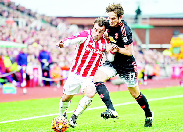 Stoke City's Swiss striker Xherdan Shaqiri (left), vies with Manchester United's Dutch midfielder Daley Blind during the English Premier League football match between Stoke City and Manchester United at the Britannia Stadium in Stoke-on-Trent, central England, on Dec 26.
