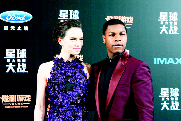 Actress Daisy Ridley (left), shares a light moment with actor John Boyega on stage as they attend the premiere of 'Star Wars: The Force Awakens' in Shanghai, China on Dec 27. 'The Force Awakens' opens in the world's second-biggest movie market on Jan 9 and producers say they anticipate it will play 'very very well' in China. (AP)