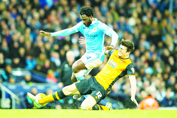 Manchester City's Wilfried Bony (top), is tackled by Hull City's Harry Maguire during the English Premier League Cup soccer match between Manchester City and Hull City at the Etihad Stadium, Manchester, England on Dec 1. (AP)