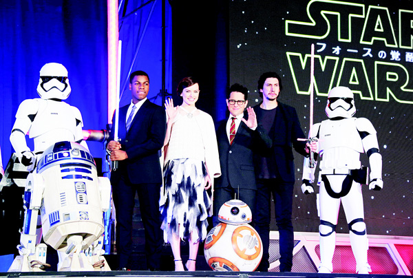 In this Dec 10 file photo, Director J.J. Abrams (third right), and actors, John Boyega (second left), Daisy Ridley (third left), and Adam Driver (second right), pose for photos during the Japan Premiere of their latest film 'Star Wars: The Force Awakens' in Tokyo. (AP)