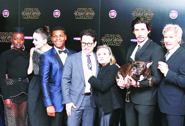 In this Dec 16, 2015 file photo, cast members, Lupita Nyong'o (from left), Daisy Ridley, John Boyega, director J.J. Abrams, Carrie Fischer, Adam Driver and Harrison Ford pose for photographers upon arrival at the European premiere of the film 'Star Wars: The Force Awakens,' in London. 'Star Wars' isn't just strong. It's unstoppable. The revival of the nearly 40-year-old space saga has already dominated the box office and toy shelves. Now, it's also been selected as The Associated Press Entertainer of the Year and is amassing support for Academy Awards consideration. (AP)