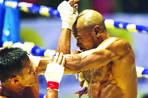 This photo is taken on Dec 20, shows Lethwei martial arts fighter Tun Tun Min (left), in the ring with his opponent, US national Cyrus 'Black Dynamite' Washington, at the Thein Phyu boxing stadium in Yangon. (AFP)