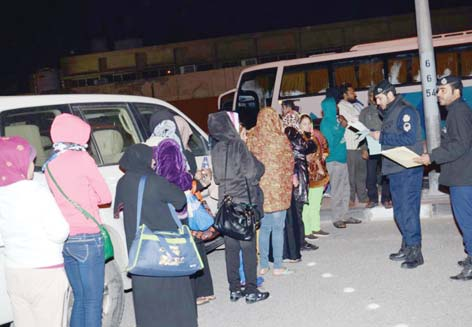 Some of the Asian women arrested for not having legal residence or other crimes are directed towards a Ministry of Interior bus. The raid was carried out early in the morning on Dec 23.