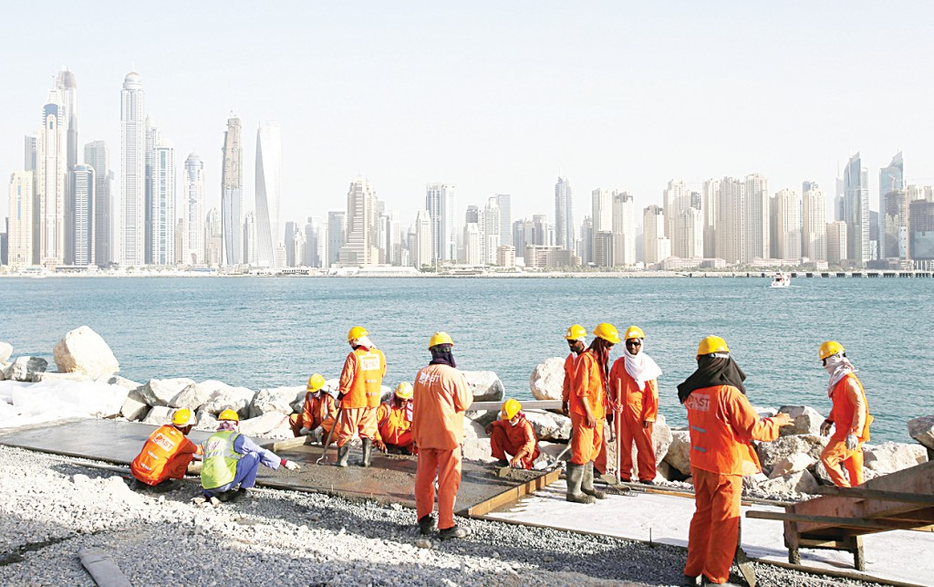 In this Sept 22, 2015 file photo, with the Marina Waterfront skyline in the background, laborers work at a construction site at the Palm Jumeirah, in Dubai, United Arab Emirates. Human Rights Watch has released on Dec 22, a set of guidelines it says construction companies working in the oil-rich Gulf Arab states should follow to ensure basic rights for migrant workers. (AP)
