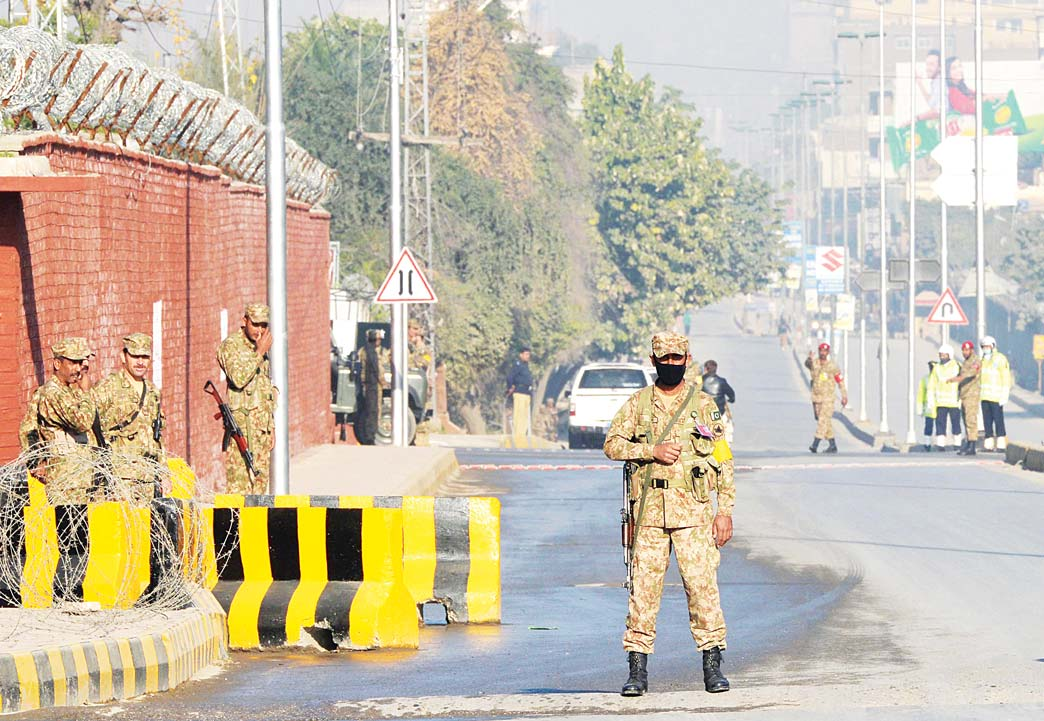 Pakistani army troops cordon off a street leading to the Army Public School due to hold a ceremony to mark the first anniversary of the school massacre which left more than 150 people dead, in Peshawar on Dec 16. (AFP)