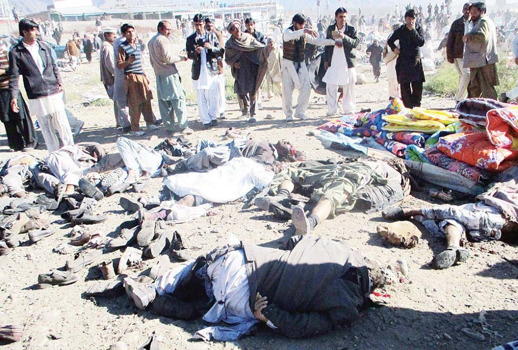 Pakistani men gather beside the bodies of victims of a bomb explosion at a market in Parachinar, the capital of Kurram tribal district, on Dec 13. (AFP)