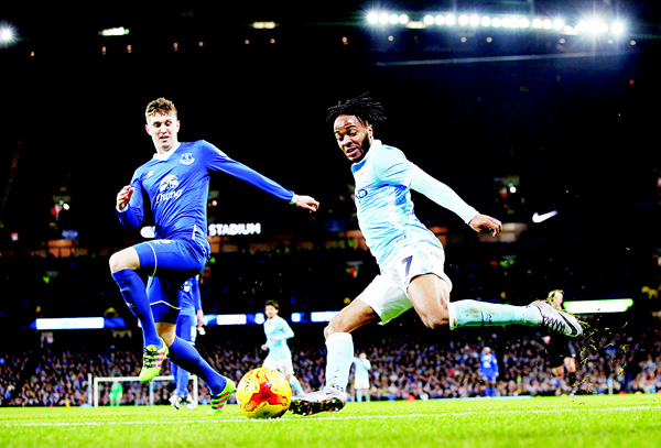 Manchester City's Raheem Sterling (right), goes to cross a ball past Everton's John Stones which replays showed rolled out of play from which Kevin De Bruyne scored their second goal from during the English League Cup semifinal second leg soccer match between Manchester City and Everton at the City of Manchester Stadium in Manchester, England on Jan 27. (AP)