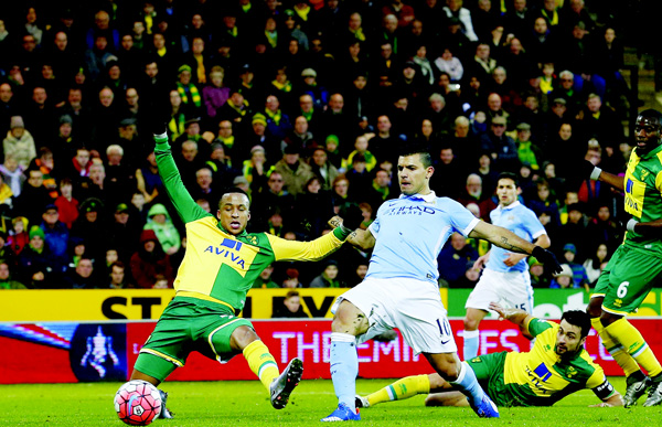 Manchester City's Argentinian striker Sergio Aguero (second left), scores his team's first goal during the FA Cup third-round football match between Norwich City and Manchester City at Carrow Road in  Norwich, eastern England on January 9. (AFP)