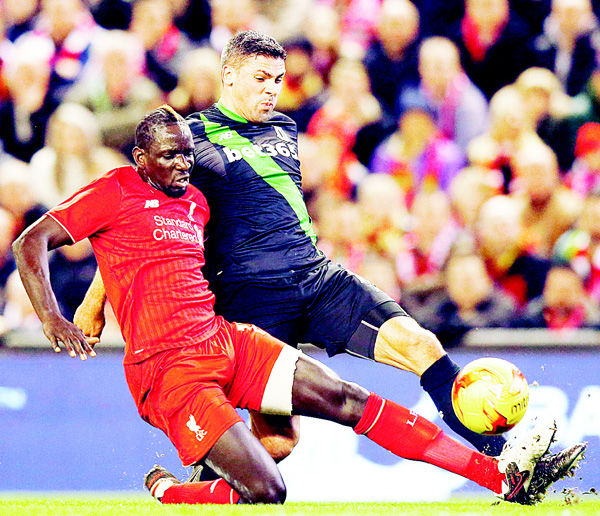 Liverpool's Mamadou Sakho (left) vies for the ball with Stoke's Jonathan Walters during the English League Cup semifinal second leg soccer match between Liverpool and Stoke City at Anfield Stadium in Liverpool, England, on Jan 26. (AP)