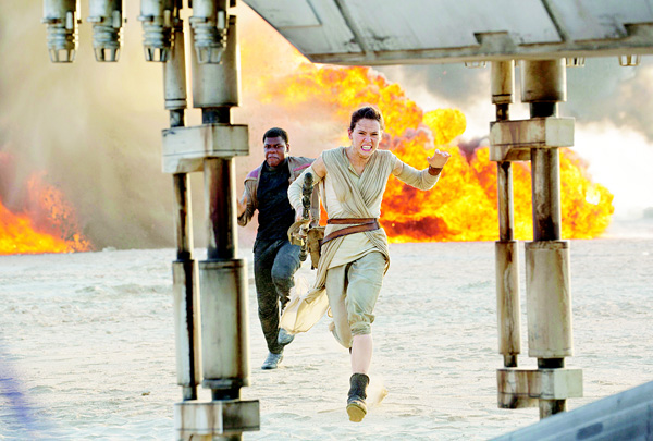 This photo provided by Disney/Lucasfilm shows Daisy Ridley (right), as Rey, and John Boyega as Finn, in a scene from the film, 'Star Wars: The Force Awakens', directed by J.J. Abrams. (AP)