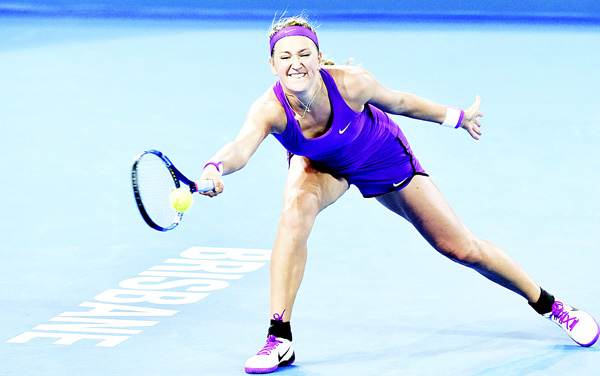 Victoria Azarenka of Belarus hits a return against Angelique Kerber of Germany during their women's final match on the seventh day in Brisbane. (Inset): Victoria Azarenka of Belarus lifts her winning trophy after defeating Angelique Kerber of Germany in the women's final match on the seventh day of the Brisbane International tennis tournament on Jan 9. (AFP)