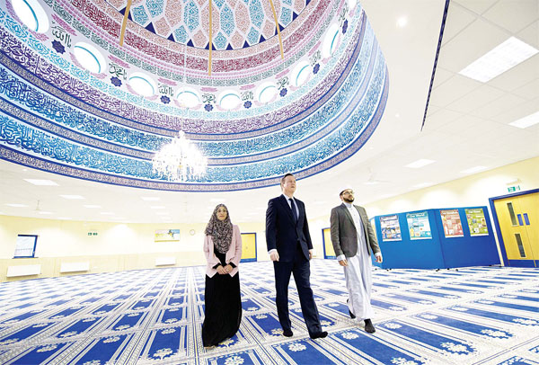 British Prime Minister David Cameron (center), talks with Imam Qari Asim (right), and Shabana Muneer, a member of Makkah Masjid Mosque's women's group, as he visits Makkah Masjid Mosque in Leeds, northern England
