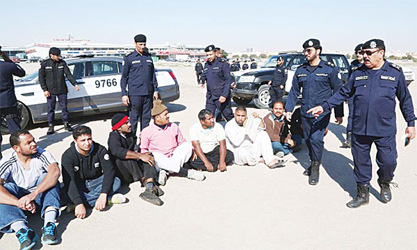 Policemen surround some of the arrested illegals