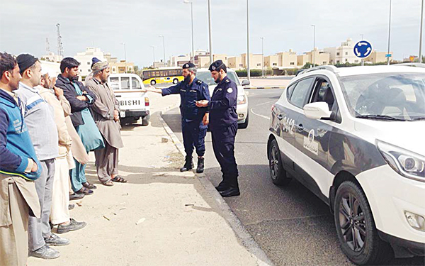 Policemen checking IDs of labourers waiting for work by the roadside
